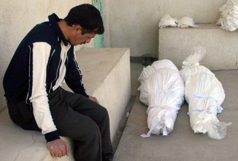 Iraqi man sits waiting to claim the bodies of his father an mother outside morgue in Kerbala's cemetary