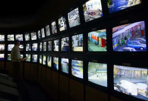 Surveillance monitoring expert stands next to a bank of screens showing images from Edinburgh City Council's network of CCTV cameras in Edinburgh