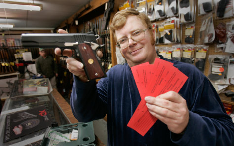 IMAGE: GUN STORE MANAGER WITH GUN RAFFLE TICKETS
