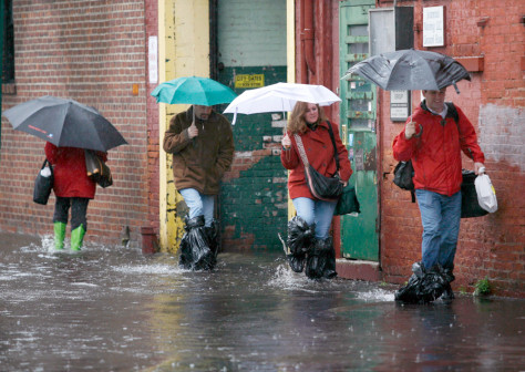IMAGE: Pedestrians walk through the flooded streets of Hoboken