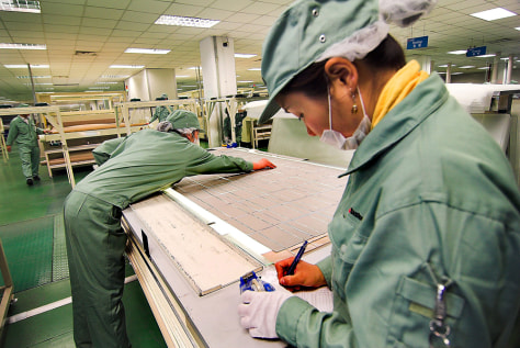 Image: Workers handle solar cells