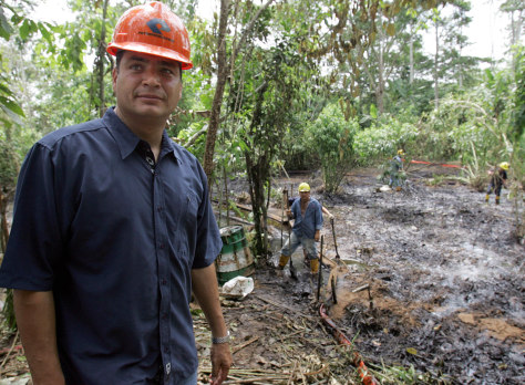 IMAGE: RAFAEL CORREA NEAR OIL-SATURATED SOIL