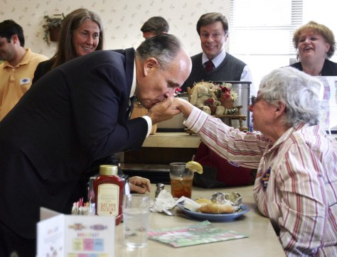 Republican presidential candidate and former New York City mayor Giuliani kisses the hand of Guenther during a campaign stop in Manchester