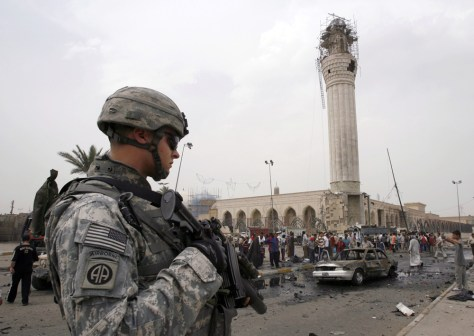 IMAGE: A U.S. soldier stands guard at site of bomb attack near a Sunni mosque in Baghdad