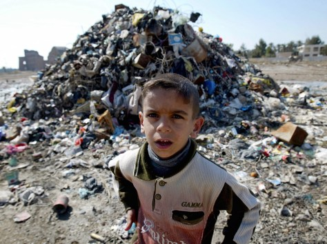 Image: Iraqi boy in front of pile of garbage