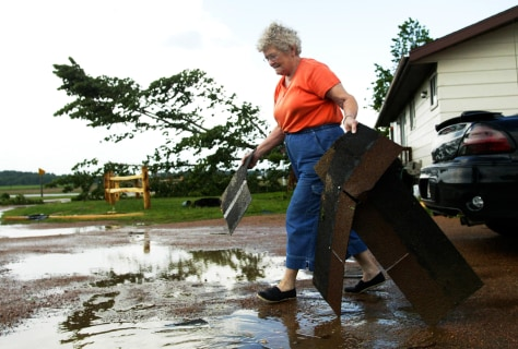 IMAGE: WOMAN CLEANS UP AFTER TWISTER