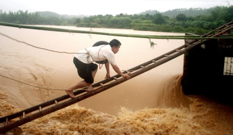 Image: Man climbing to floodgate