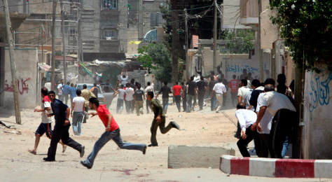 IMAGE: Palestinians run for cover