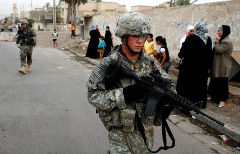 U.S. soldiers walk past Iraqi women with their children during a patrol in Baghdad