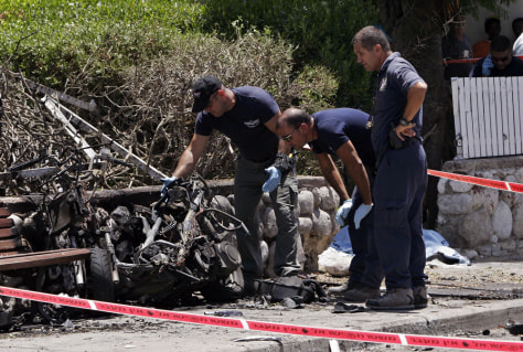 IMAGE: Israeli police examine a motorcycle that exploded killing Arik Korkus.