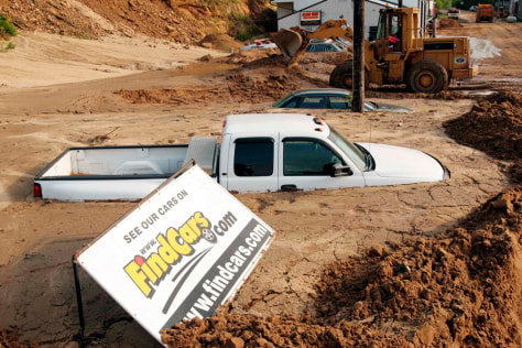 IMAGE: Heavy equipment used to dig out used cars buried in silt.