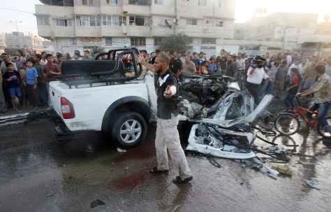 Image: Palestinians gather around the wreckage of a vehicle