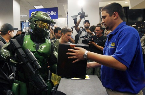 "Dressed as the character Master Chief from the Xbox 360 video game ""Halo 3"", gaming fan Jim Cush purchases his copy of the game during a midnight sales event in New York"