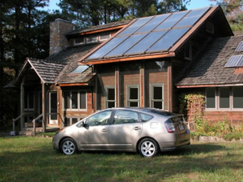 IMAGE: HYBRID CAR IN FRONT OF SOLAR HOUSE