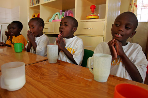 HIV positive orphans pray before having a glass of milk at Nyumbani hospice in Nairobi
