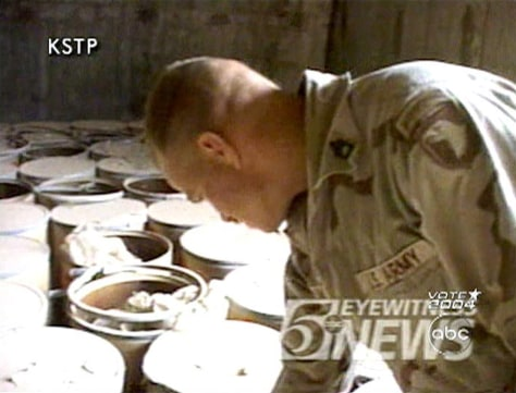 Image: Soldier examines contents of a barrell.