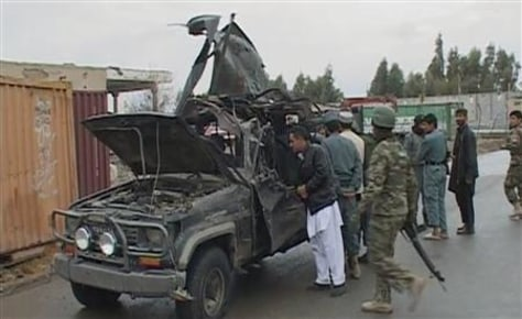 A video grab shows security personnel examining the damaged vehicle belonging to the deputy governor of Afghanistan's southern Kandahar province, after an attack in Kandahar city