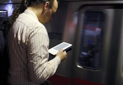 Image: A commuter reads on his Kindle e-reader