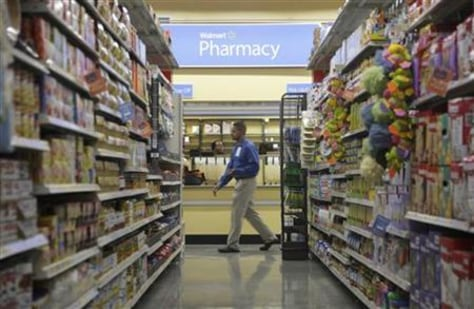 A worker walks past the pharmacy in a new Walmart Express store in Chicago