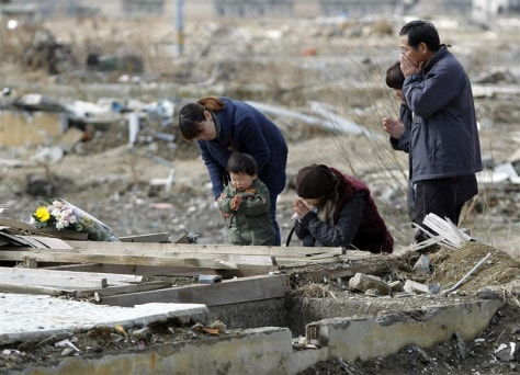 Image: A Japanese family prays Sunday for a brother and his family killed by the March 11, 2011, earthquake and tsunami, in Ishinomaki, Miyagi prefecture.