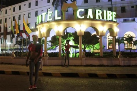 Image: Prostitutes walk in front of the Hotel Caribe in Cartagena, Colombia