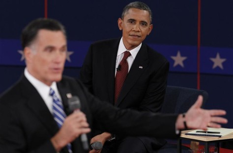 U.S. President Obama listens as Republican presidential nominee Romney answers a question during the second presidential debate in Hempstead