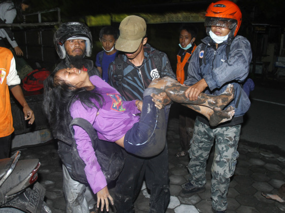 Image: Villagers carry a woman as they flee their homes following another eruption of Mount Merapi