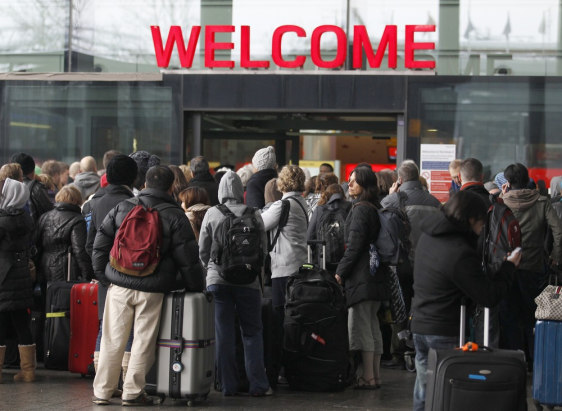 Image: Airline passengers line up to enter the departures area at Terminal 3 at Heathrow Airport in west London