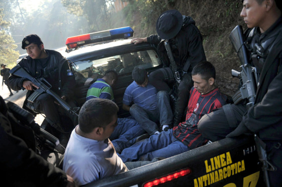 Image: Guatemalan police load four suspects into a pickup truck