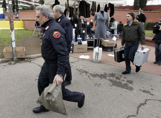 Image: Carabinieri carry equipment outside the underground train station where an explosive device was found, in Rome.