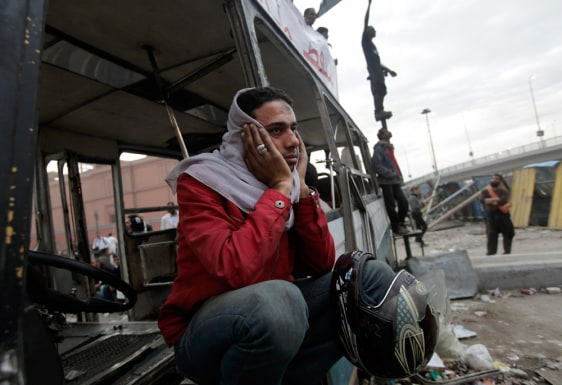 Image: Egyptian protester sits in a damaged vehicle