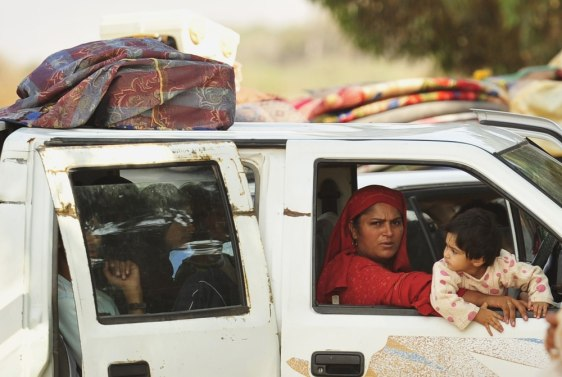 Image: A family fleeing from the fighting between pro-Gaddafi and anti-Gaddafi forces drive pass Khamseen Gate