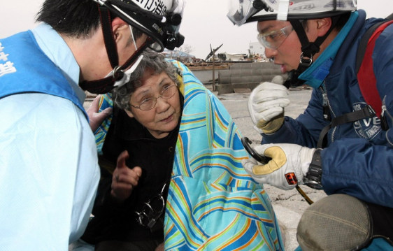 Image: Eighty-year-old Sumi Abe is wrapped in a blanket after being rescued from the wreckage of her home for nine days