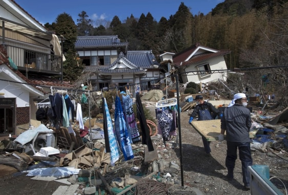 Image: The laundry of residents of Oshima island dry on a line as they carry Japanese tatami mats