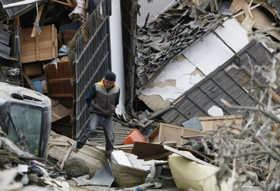 Image: Man walks on debris in Ishinomaki city, Miyagi prefecture
