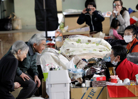 Image: Japan's Emperor Akihito and Empress Michiko talk with an evacuee at an evacuation center in Kazo, Saitama Prefecture, Japan