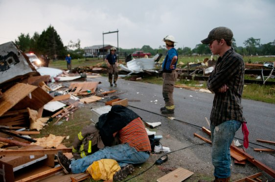 Image: Firefighter covers survivor of a twister