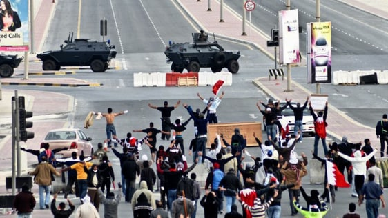 Image: Anti-government protestors open their arms in front of military vehicles