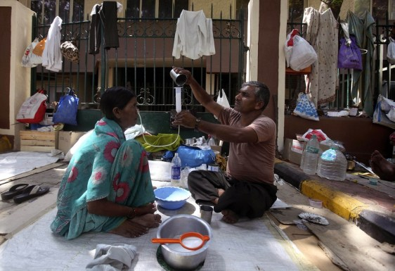 Image: Ananada, right, feeds milk through a food pipe to his cancer patient wife Mangalabai in Mumbai, India.