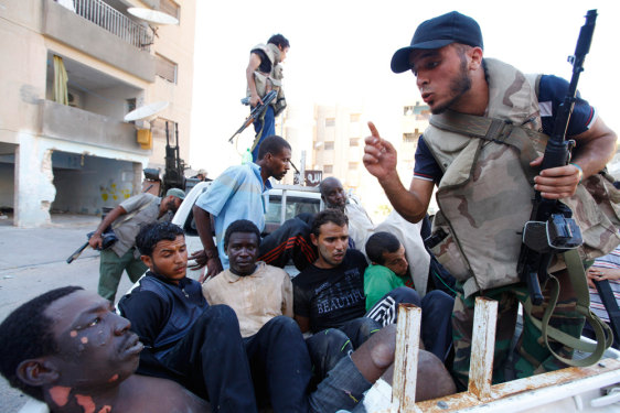 Image: Libyan rebel fighters stand guard over detainees in Tripoli