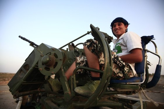 Image: Anti-Gaddafi fighter smiles as he waits outside the town of Bani Walid