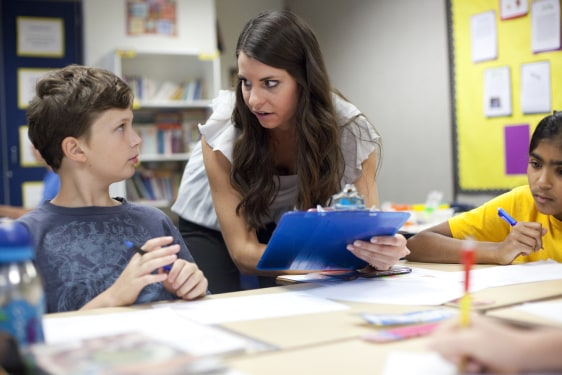 Image: Teacher Amy Esmay, 23, helps students Noah Galen, left, and Meghna Shankar in her classroom