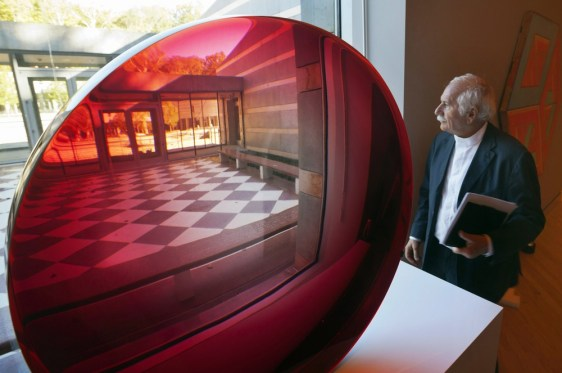 Image: Architect Moshe Safdie stands next to a sculpture by artist Fred Eversley at the Crystal Bridges Museum of American Art in Bentonville, Ark.