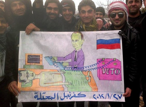 Image: Syrians pose with a cartoon depicting the Russian Prime Minister Vladimir Putin defibrillating Syrian President Bashar al-Assad