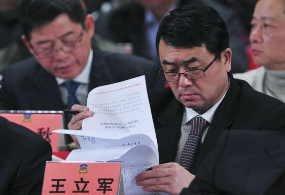 Image: Wang Lijun reads documents as he attends a session of the Chinese People's Political Consultative Conference (CPPCC) last month.