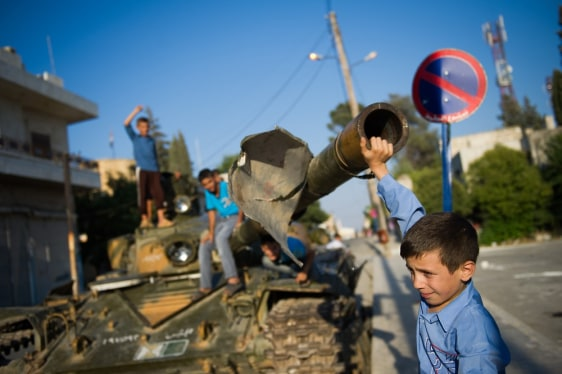 Image: A Syrian boy plays with a tank in the to