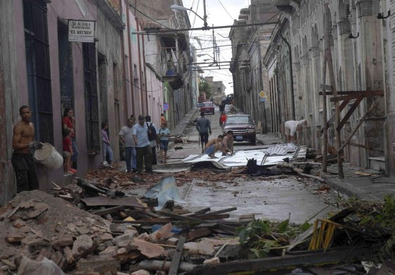 Image: People walk near to a damaged building in Santiago de Cuba