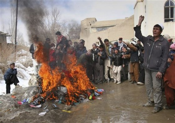 Image: Afghans burn blankets, clothing and other items that were distributed by coalition troops