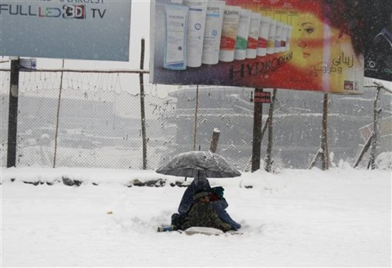 Image: An Afghan woman wearing a burqa waits for alms with her child during a snowstorm in Kabul