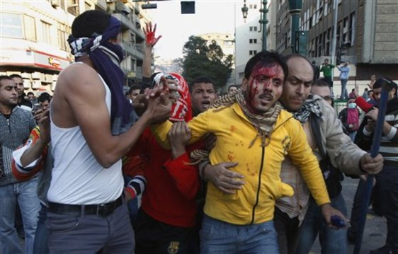 Image: Protesters help wounded man in Tahrir Square